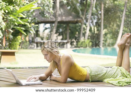 Attractive blonde woman using a laptop computer while laying down on a wooden deck in a tropical garden. - stock photo