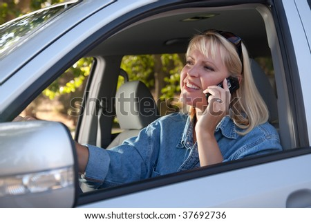 Attractive Blonde Woman Using Cell Phone While Driving - stock photo
