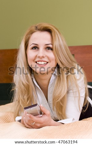 attractive blonde woman watching tv  in her living room - stock photo