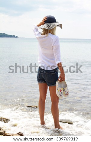 Attractive Blonde Woman wearing white shirt and straw standing and enjoying view on the beach near sea - stock photo