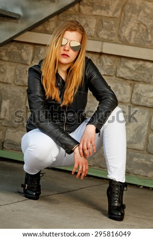 Attractive blonde woman with leather jacket and reflective sunglasses - stock photo
