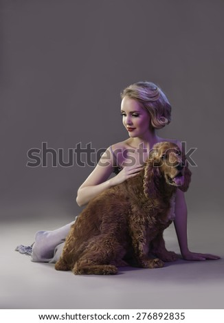 Attractive blonde woman with red lips sitting next to cute dog - stock photo