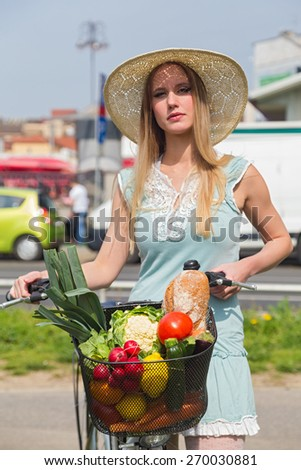 Attractive blonde woman with straw hat posing next to bike with basket full of groceries. - stock photo