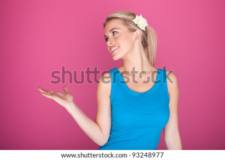 Attractive blonde women looking at her empty palm ready for the placement of your product for advertising and retail, studio on pink