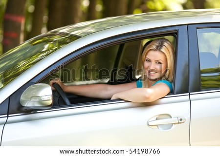 Attractive blonde young woman at the wheel in her new car - stock photo
