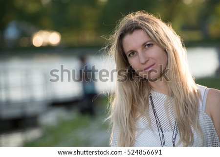 Attractive blonde young woman in a park with blurred background
