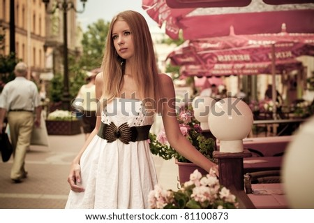 Attractive blonde young woman on the street - stock photo