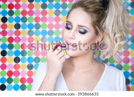 Attractive blonde young woman putting on lipstick on spotted background, make up beauty and fashion concept  - stock photo