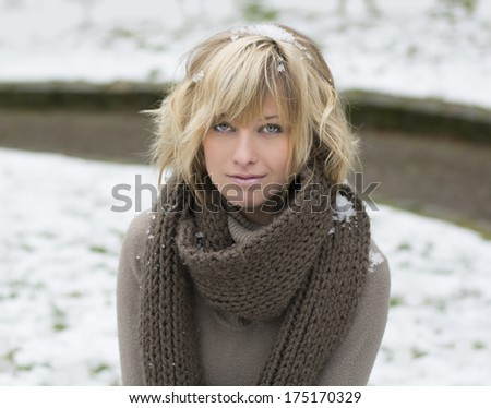 Attractive blonde young woman with wool scarf, snow around her - stock photo