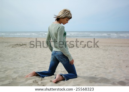 Attractive blong girl alone on the beach - stock photo