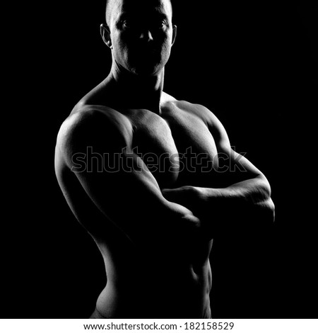Attractive body builder posing and showing off muscles on dark background. - stock photo