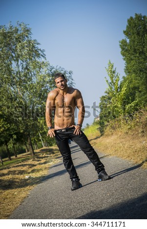 Attractive bodybuilder shirtless outdoor showing torso muscles, abs, pecs and arms, looking at camera in tilted photo - stock photo