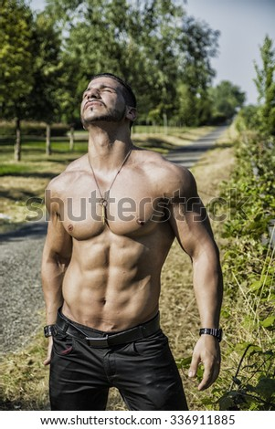 Attractive bodybuilder shirtless outdoor showing torso muscles, abs, pecs and arms, with eyes closed - stock photo