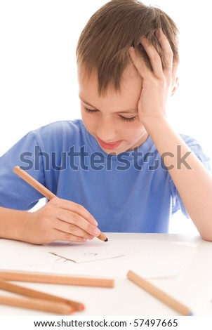 Attractive boy drawing a picture at the desk