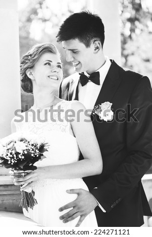 attractive bride and groom kissing, sitting on a bench, black and white image
