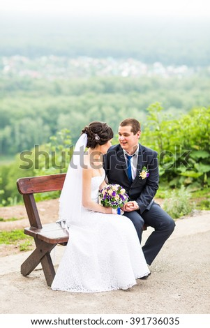 attractive bride and groom  sitting on a bench