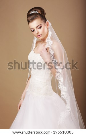 Attractive Bride in White Dress and Openwork Veil Daydreaming - stock photo