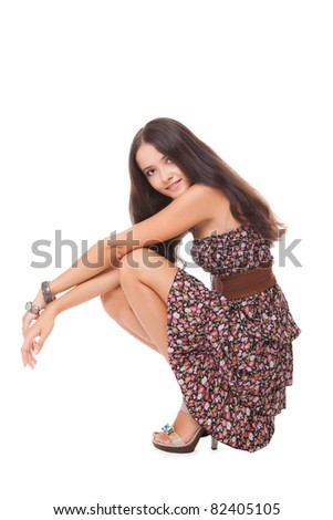 attractive bright young woman squatting on white background - stock photo