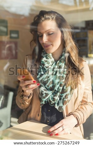Attractive brown-haired woman relaxing in a local bar, texting a message on a smart phone. - stock photo