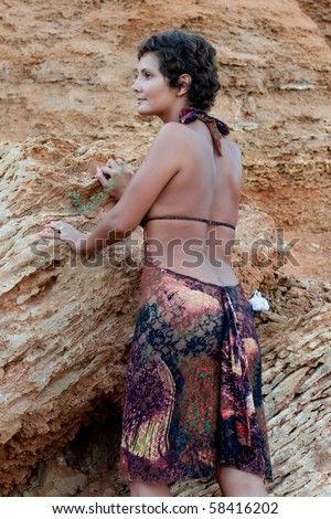 attractive brunet woman in brow dress among rocks in the hot desert