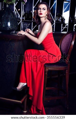Attractive brunet woman with long hair in elegant red dress sitting on bar stool.