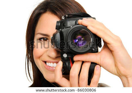 Attractive brunette aims her camera. composing a photograph in studio, isolated on white