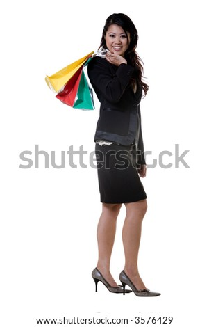 Attractive brunette Asian smiling business woman wearing black business suit holding colorful bags standing on white - stock photo