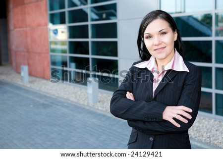 attractive brunette businesswoman in front of office - stock photo