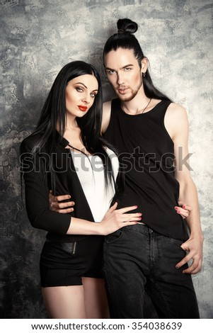 Attractive brunette couple in black clothes posing over grunge background. Fashion shot.