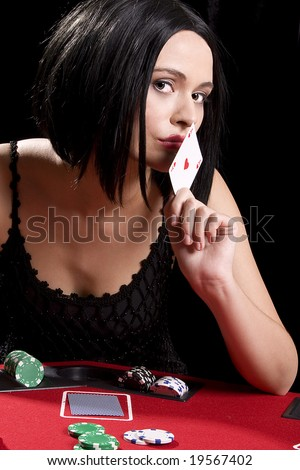 Attractive brunette dressed as a new york gangster kissing the ace of hearts - stock photo