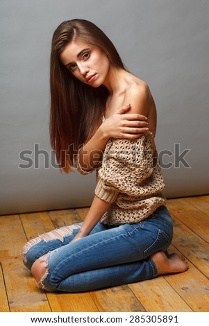 attractive brunette fashion model woman with naked shoulder sitting on the wooden floor over gray background - stock photo