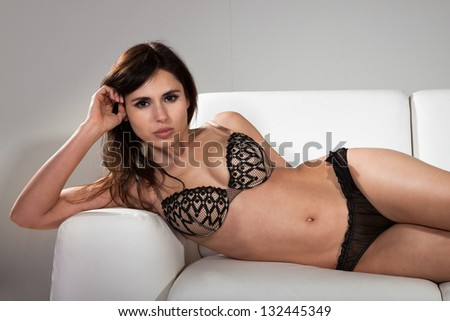 Attractive Brunette Female In Lingerie Lying On A Couch
