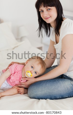 Attractive brunette female posing with her baby lying on her while sitting on a bed - stock photo