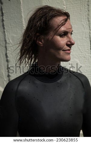 Attractive brunette female swimmer wearing black wetsuit with wet hair and looking calmly with slight smile and sunlight in face - stock photo