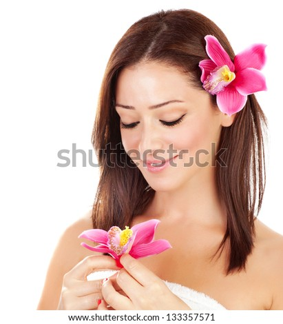 Attractive brunette female with pink orchid flowers in hair isolated on white background, cute girl with closed eyes enjoying day spa - stock photo