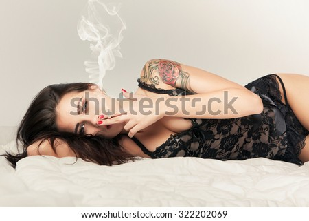 attractive brunette girl in bed with cigarette - stock photo