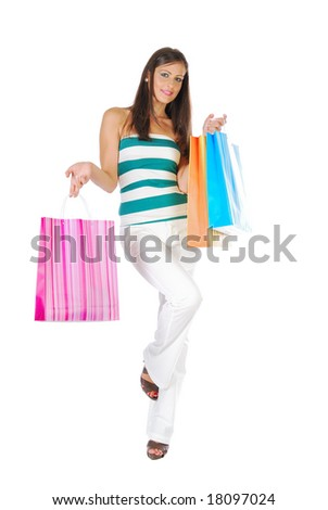 Attractive brunette girl in casual/sports clothing showing colorful shopping bags, isolated on white - stock photo