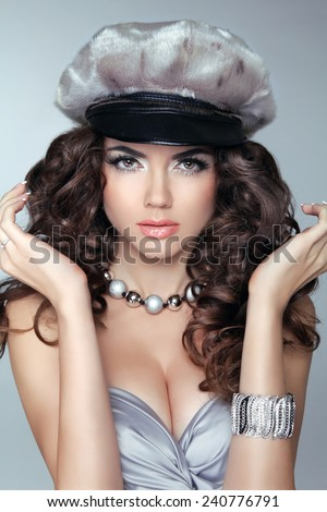 Attractive brunette girl model in fashion hat with long wavy hair styling, makeup and jewelry isolated on gray background - stock photo
