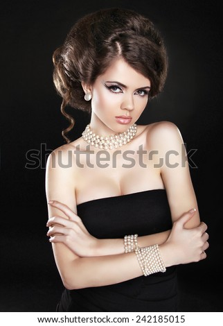 Attractive brunette girl model with hair styling, makeup and fashion jewelry isolated on dark background - stock photo