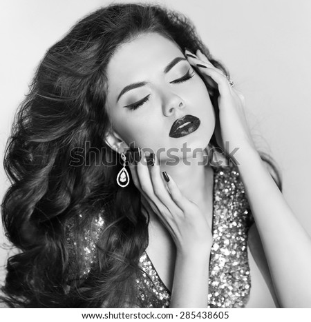 Attractive brunette girl model with long wavy hair styling, makeup and fashion jewelry isolated on gray background. Black and white portrait. - stock photo