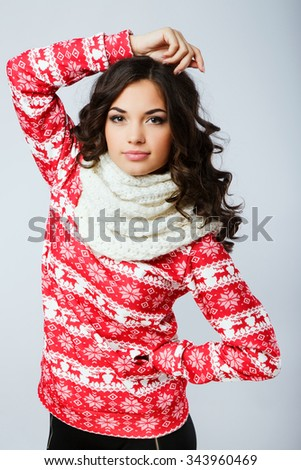 Attractive brunette girl, with curly hair, wearing in red Christmas sweater and white scarf, posing with hand on her head, on the white background, in studio, waist up