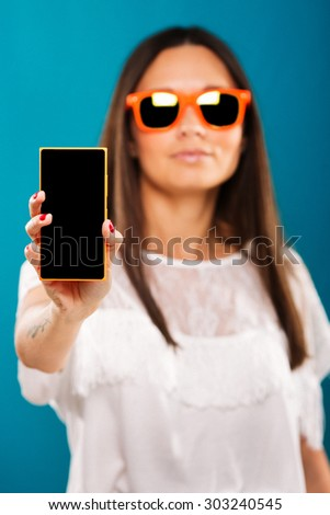 Attractive brunette girl, with long straight hair, wearing in white blouse, and orange sunglasses, is holding smart phone in her hand, on blue background, waist up - stock photo
