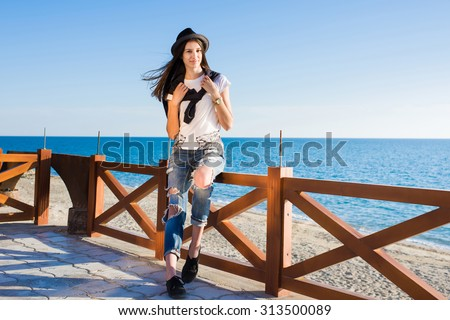 Attractive brunette hair woman dressed in stylish clothes enjoying good sunny weather during promenade, gorgeous hipster girl rest outdoors while strolling along the seashore in spring season - stock photo