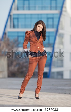 Attractive brunette in brown suit outdoors. Young business woman posing on open air