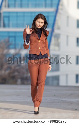 Attractive brunette in brown suit outdoors. Young business woman walking along city looking at camera