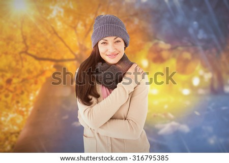 Attractive brunette looking at camera wearing warm clothes against autumn changing to winter