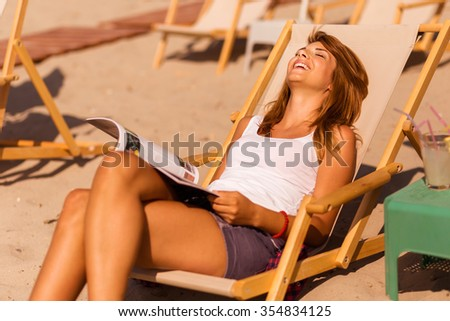 Attractive brunette lying on a sunbed on a beach, reading a magazine and enjoying the sun - stock photo