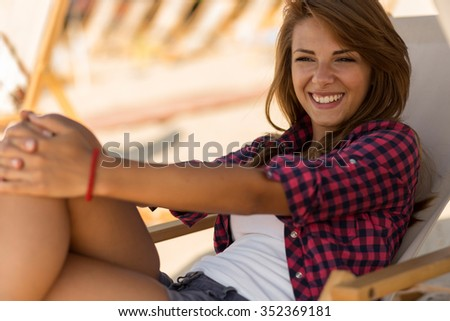 Attractive brunette lying on a sunbed on a beach under a parasol enjoying the day - stock photo