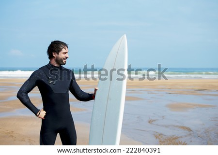 Attractive brunette man dressed in wetsuit ready to surfing on big ocean waves at sunny autumn day, young professional surfer smiling standing on beautiful ocean beach with his white surfboard - stock photo