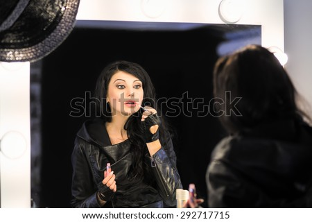 Attractive brunette painting her lips in front of the mirror - stock photo